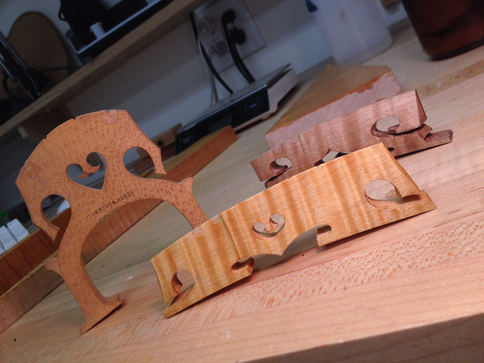 "Hand cut cello bridge, the new ""improved"" Amati bridge and the older Amati bridge in the rear"